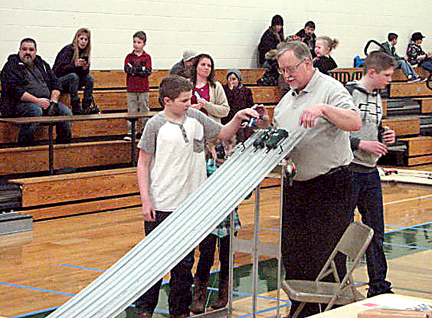 News Photo by Tyler Winowiecki Gunner Weaver hands his pinewood derby car to Dave Fisher during the fourth annual Ranger Derby at Atlanta Elementary Saturday. Weaver would end the day with a second place finish in his fifth grade division.