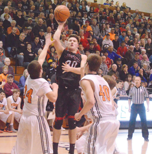 News Photo by Jonny Zawacki Powers North Central's Jason Whitens (30) makes a shot while being defended by Hillman's Kory Henigan (40) and Chris Wittman (34) in the quarterfinal game at Sault Saint Marrie High School on Tuesday.