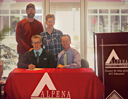 Courtesy Photo Levi Goebel (front, left) signs his Letter of Intent to continue his athletic career with the ACC Cross Country team coached by Mark Jacobs (front, right) while his parents Kory and Lisa Goebel look on.