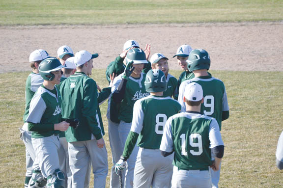 News Photo by James Andersen Alpena's Logan Guthrie (center) is mobbed by teammates after driving in the winning run in a game against Rogers City on Thursday at Alpena High School.