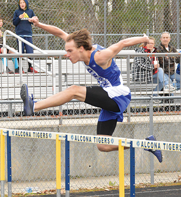 News Photo by James Andersen Oscoda's Michael Stadler leaps over a hurdle during the boys 110 hurdles. Stadler won the event, finishing in 18.08 seconds.