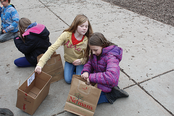 News Photo by Jordan Spence  Liberty Prevost, 10, and Madisynne Wirgau, 10, play a game where they sort trash and recyclables Friday at Besser Elementary school.