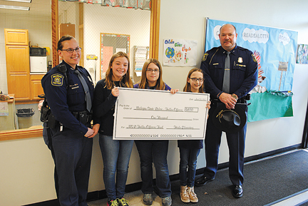 News Photo by Jason Ogden Left to right, Michigan State Police Alpena Post Commander John Grimshaw, Hinks Elementary students Cecelia Magdeleno, Avery Dubey, Lilly Gembel and Trooper Ashley Simpson pose for a photo during a check presentation Friday. Students at the school, through the Coins for Cops program, raised $1,000 for the Michigan State Police Fallen Trooper Fund.