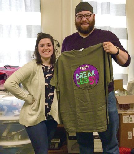 News Photo by Diane Speer Paige and Jeffrey Mindock of Thunder Bay Theatre show off a t-shirt from last year's inaugural Break a Leg 5K.