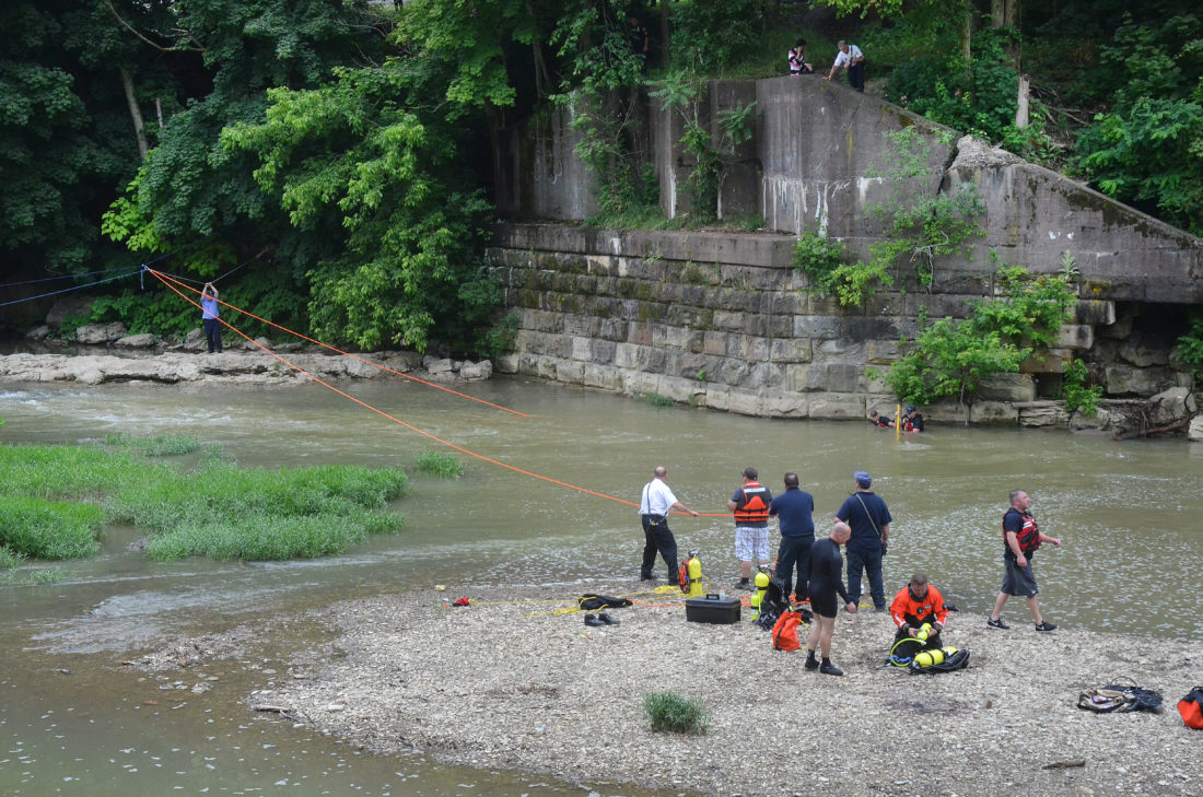 Emergency personnel search for 8-year-old Emanual Williams after he fell into Big Wheeling Creek Thursday.