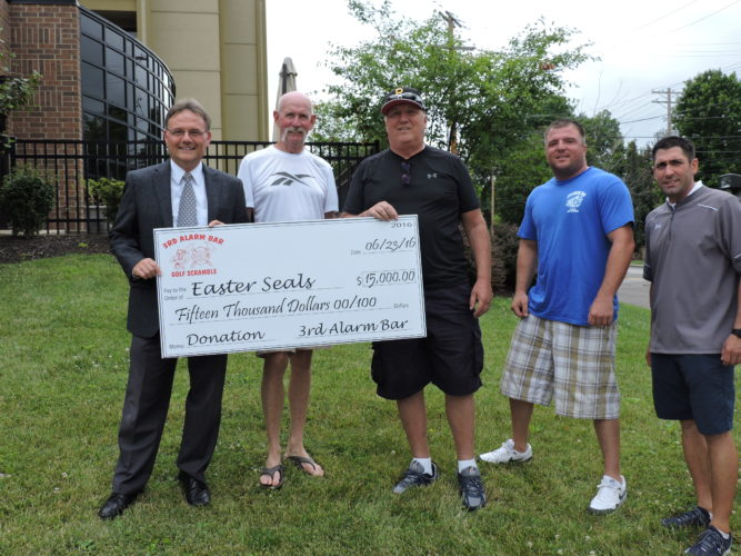 Photo by Jackie McDermott Easter Seals CEO Jay Prager, left, accepts a $15,000 donation from the Third Alarm Bar on Wheeling Island, representing proceeds from the business's annual golf scramble. Making the donation, from left, are event co-chairmen Tom Dorsch and bar owner Tom Vapner, and Nate Vapner and Tony Chiazza.