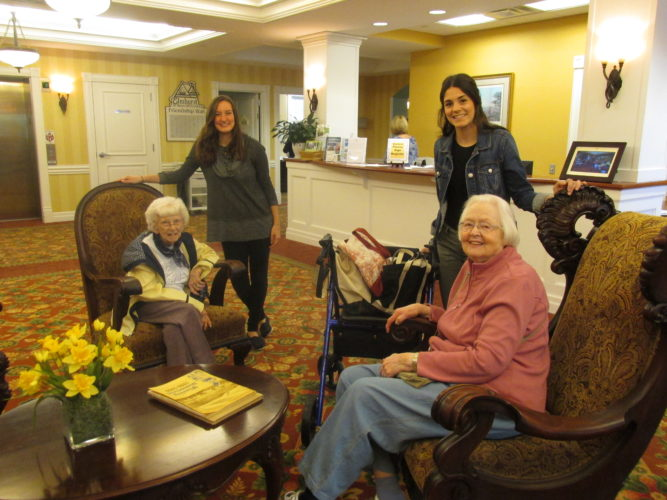 Meg Haller, standing left, and Sarah Shia, standing right, visit with Betsy Higgins, left, and Rachael Davis in the lobby of Elmhurst in Wheeling. The West Virginia University sophomores and best friends from Wheeling are spending three days a week this summer interning at the senior living residence.