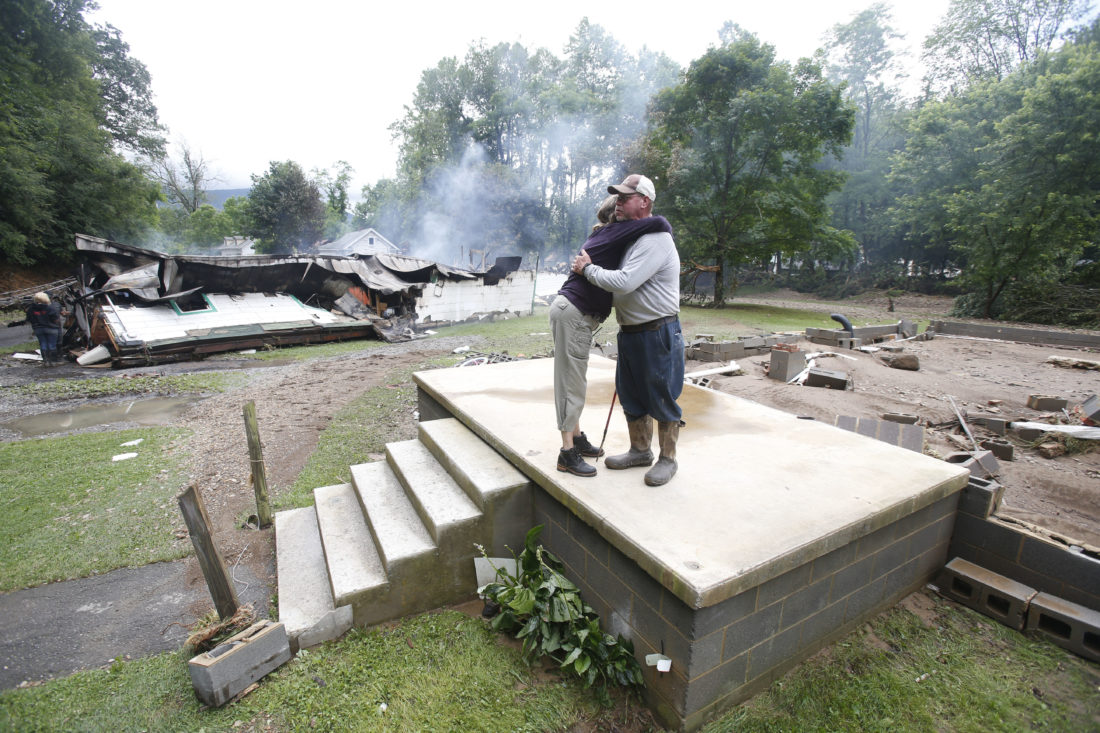 AP Photo / Jimmy Scott gets a hug from Anna May Watson, left, as they clean up from severe flooding in White Sulphur Springs, W.Va., Friday. Scott lost his home to the flood and a fire that consumed his home and the homes of several relatives.