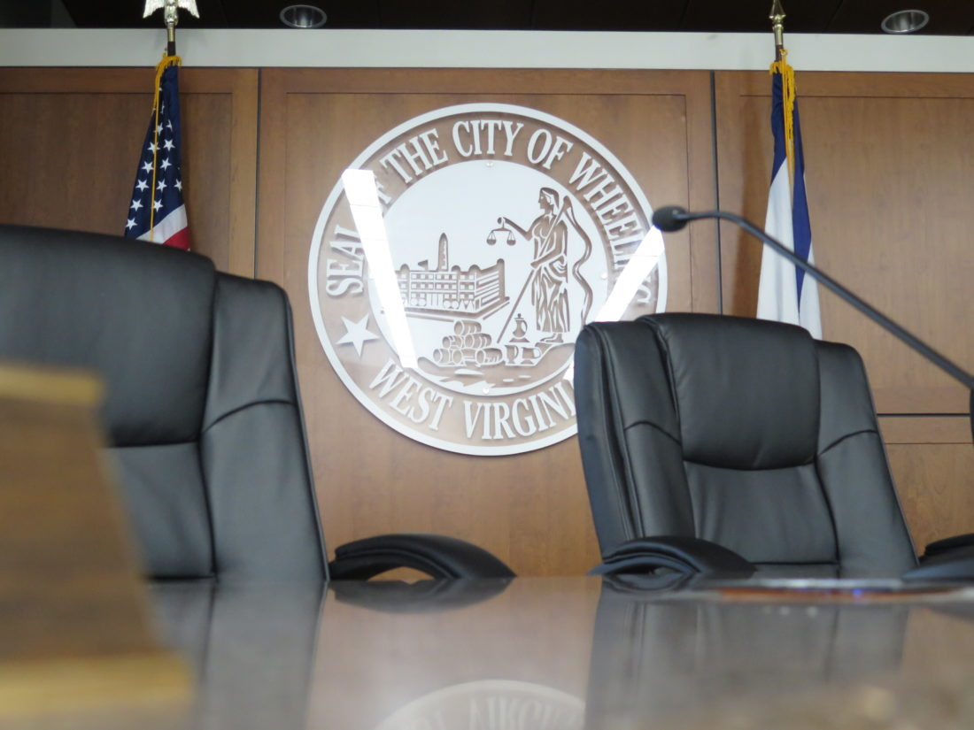 Photo by Alec Berry The seal of the city of Wheeling overlooks empty chairs in council chambers at the City-County Building.