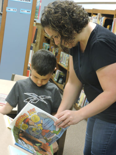 Photo by Drew Parker / Local mother Jennifer Crow helps her son, Brayden, choose a book for the summer reading program at the Marshall County Library in Moundsville.