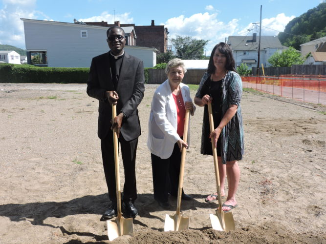 Photo by Drew Parker St. John Catholic Church pastor, the Rev. Bekeh Utietiang, left, church secretary Judy Forster, center, and parish council chair Theresa Gretchen attend a groundbreaking ceremony Tuesday for a new church building to replace the one destroyed by fire last year.