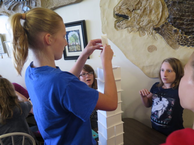 Photos by Betsy Bethel Rachel Simon, left, places the pinnacle of her team's index card tower on Tuesday during Girls Enjoying Math and Science camp at the SMART Centre Market in Wheeling, while teammates Vivian Bloomfield, center, and Grace Shanley watch.