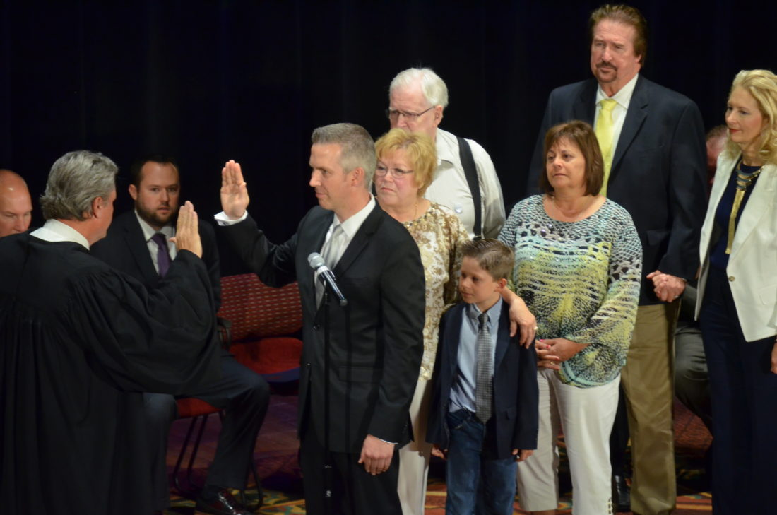 Photo by Scott McCloskey Circuit Judge David Sims swears in Glenn Elliott as Wheeling's new mayor while members of Elliott's family look on during a ceremony today at the Capitol Theatre. Council members also were sworn in during the ceremony.