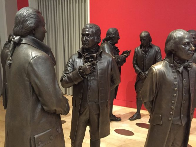 Life-size bronze sculptures   of the signers of the             U.S. Constitution are seen in the Signers' Hall at the National Constitution      Center. The room is designed to give visitors a sense of what it was like for the Founding Fathers to huddle in a room debating and writing the document.  The photo at far right shows a cut-out paper        silhouette of George        Washington on display at the Powel House, a historic site in Philadelphia, with site manager Jennifer Davidson reflected in the glass. The Powel House         was a place where                 Washington and others socialized in the late               18th century.    AP Photos