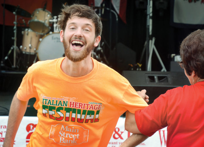 Photo by Scott McCloskey Upper Ohio Valley Italian Heritage Festival volunteer Ryan LaBelle dances in front of the main stage Friday following the opening ceremony.