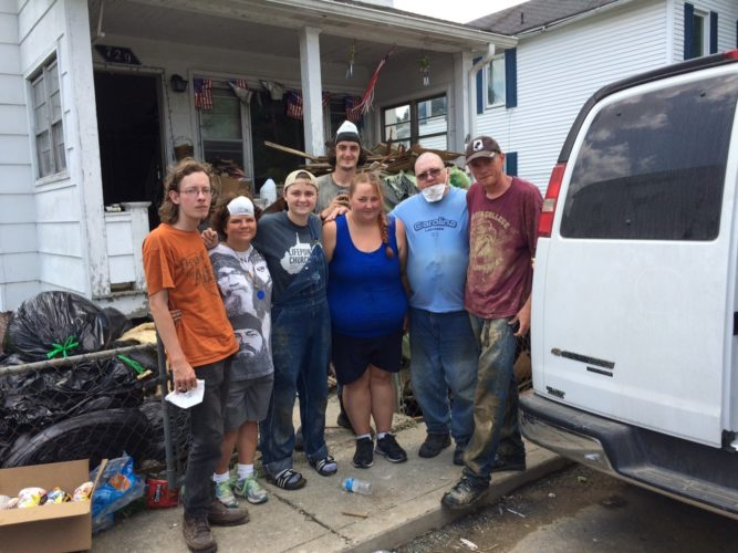 This photo provided by Haley Curtin and taken Wednesday, July 13, 2016, shows Kassie Tolley, center, in shorts, and members of the Clarksburg Mission outside Tolley's home in Rainelle, W.Va. Tolley's home was damaged by flooding on June 23, 2016. Members of the mission helped her clean up the home after meeting her by accident at a church where she had gone to look for a replacement shovel. (Haley Curtin via AP)