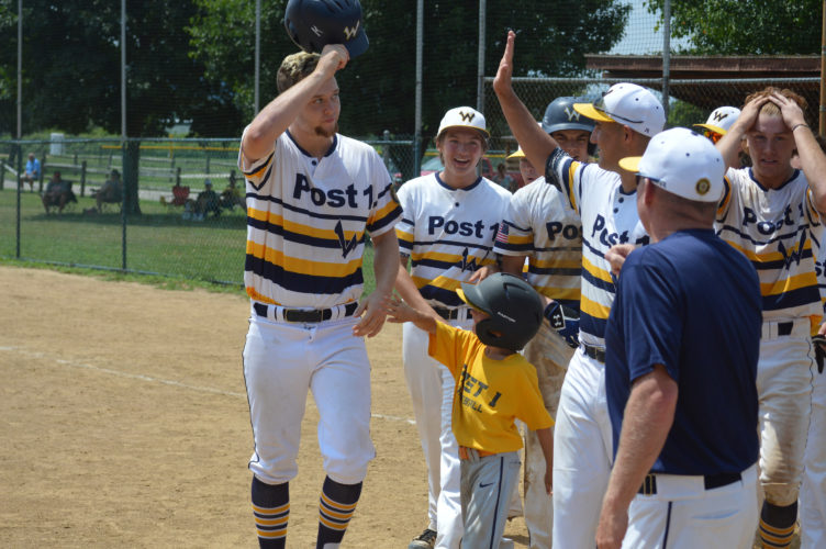 Photo by Cody Tomer Brian Campbell, left, tips his cap as he is greated by teammates after hitting a home run in the seventh inning of Wednesday's state tournament game at Moundsville.