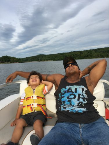 Myles and Victor Williams relax on a boat ride on Senecaville