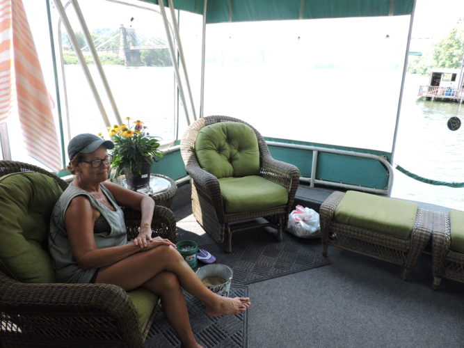 Photos by Jackie McDermott Barb Blazer lounges on the screened-in front porch of her house boat.