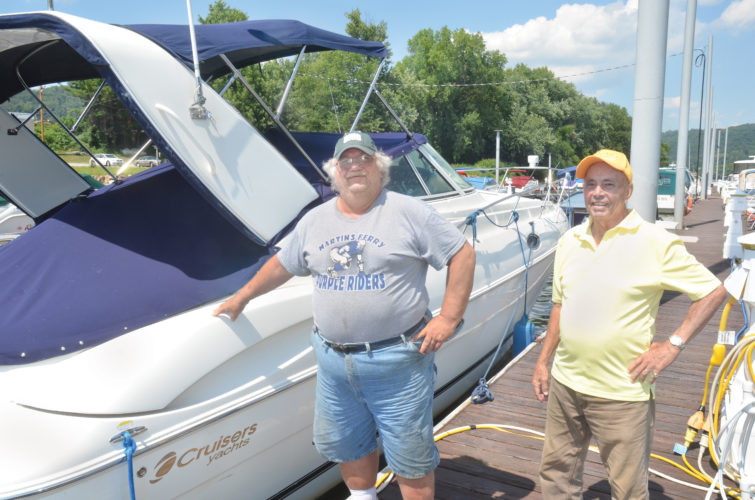 Martins Ferry Yacht Club members George Petterson, left, and Steve Cuddihy stand next to Patterson's yacht at the marina.