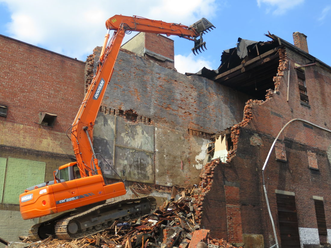 Photo by Alec Berry An excavator tears into the former Chinese Panda Kitchen building on Market Street Friday.