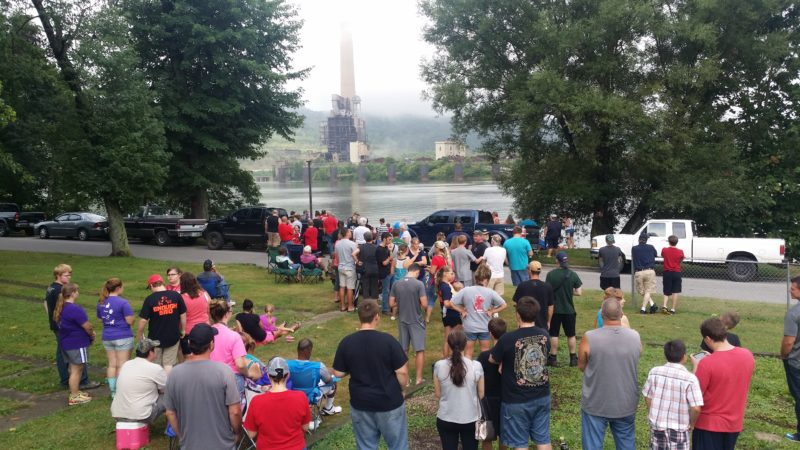 Photo by Alan Olson A crowd gathers in Moundsville on a foggy Friday morning to watch the demolition of the smokestack.
