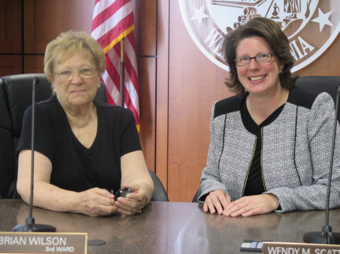Photo by Joselyn King Former Wheeling Councilwoman Gloria Delbrugge, left, and current Councilwoman Wendy Scatterday share a moment in council chambers at the City-County Building.