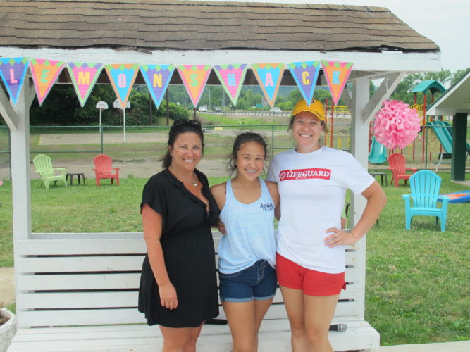 Photo by Alan Olson Sabrina Thorn, 12, center, with mother Dee Dziorney, and lifeguard Kimberly Wolfe, helps keep the McMechen city pool's lemon shake stand active on the weekends.