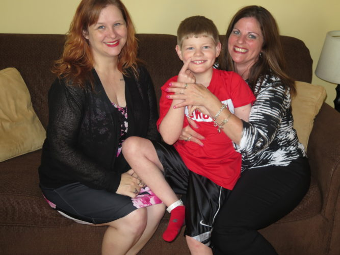 Photo by Betsy Bethel A Project Lifesaver band can be seen on the ankle of Kouper Elliott, 11, as he poses with his mother, Pat Elliott, right, of Bethlehem, and Claudia Raymer, executive director of the Ohio County Family Resource Network. Raymer's agency administers the grant that paid for Kouper's transmitter.