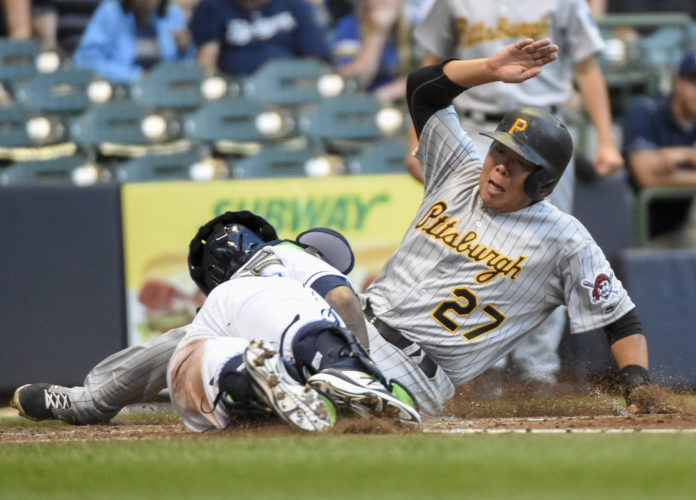 Milwaukee Brewers catcher Martin Maldonado, left, tags out Pittsburgh Pirates' Jung Ho Kang during the fourth inning of a baseball game Saturday, July 30, 2016, in Milwaukee. (AP Photo/Benny Sieu)