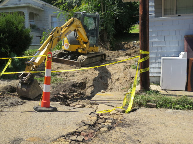 Photo by Joselyn King A large hole remains Monday in the area of 3714 Monroe St. in Bellaire following a massive 20-inch waterline break Saturday evening. A boil order remains in effect for Bellaire water customers until at least late afternoon today.