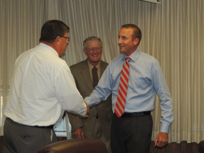 Photo by Drew Parker Casey Storm, right, accepts the open assistant principal position at John Marshall High School Tuesday. With him are Marshall County Board of Education Vice President Thomas Gilbert, left, and board member John Miller.