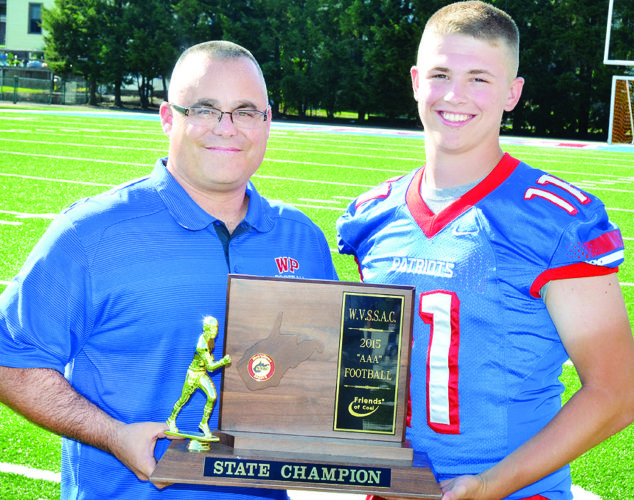 Photo by Scott McCloskey Wheeling Park High School head football coach Chris Daugherty holds the school's 2015 Class AAA football championship trophy with junior quarterback Cross Wilkinson. Wheeling Park sets out in defense of its crown this week with a Friday evening tilt against Perry, Pa.