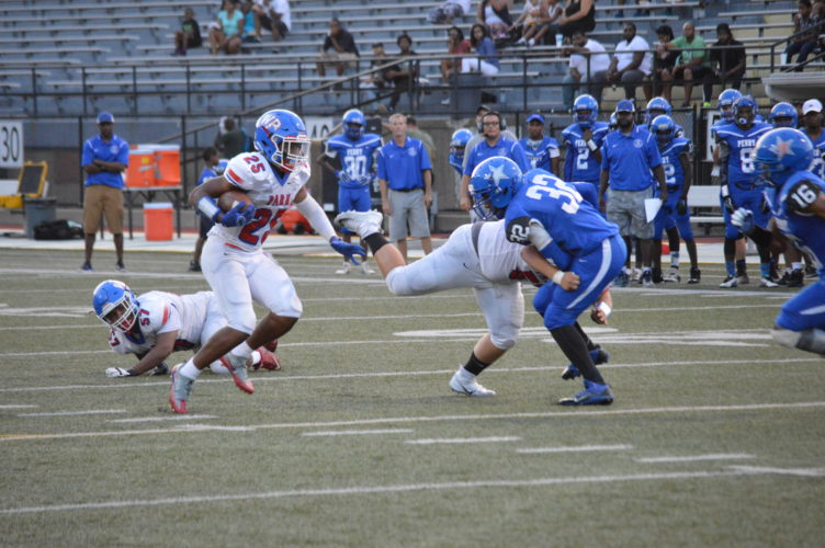 Photo by Josh Strope / Wheeling Park's Rennie Clark (25) looks for a path through the Perry Traditional defense Friday at George Cupples Stadium.