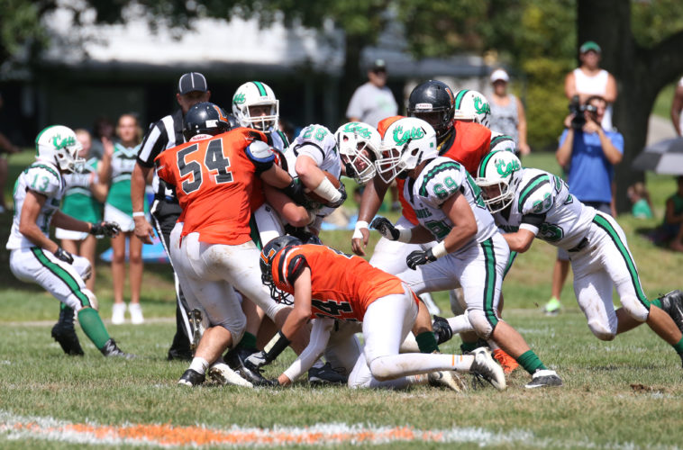 Photo by Alex Kozlowski Linsly's Stephen Snyder (54) and Eli Petho assist each other with a tackle on Mogadore's Cade Ambrose (28).