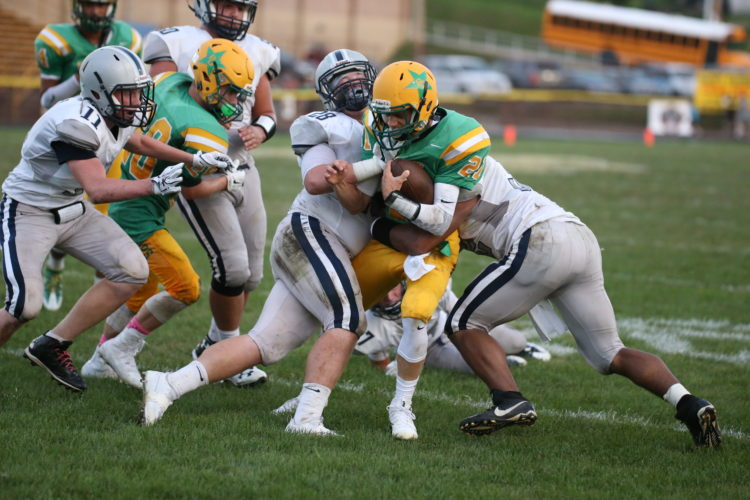 Photo by Alex Kozlowski Bishop Donahue quarterback Jimmy Hull (21) is hit by Madonna's Ryan Ekey (28) during Saturday night's game.