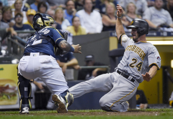 Pittsburgh Pirates' Eric Fryer, right, scores on a base hit by Josh Harrison as the ball gets by Milwaukee Brewers catcher Martin Maldonado, left, during the fourth inning of a baseball game Saturday, Aug. 27, 2016, in Milwaukee. (AP Photo/Benny Sieu)