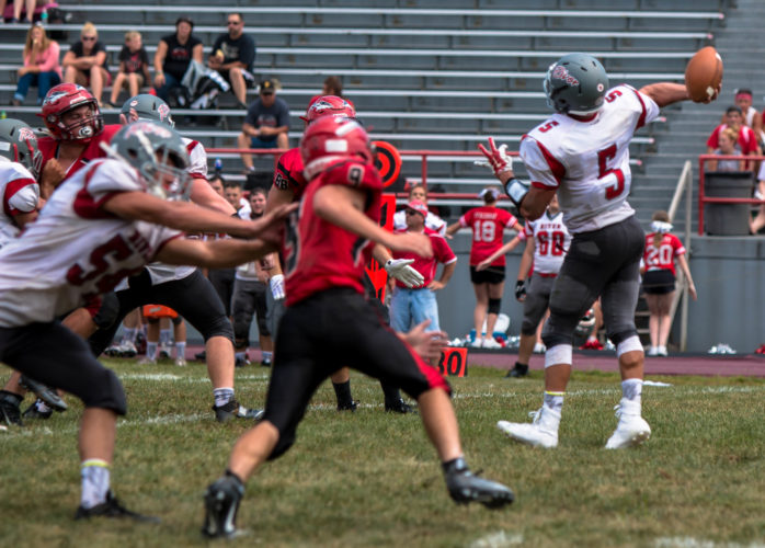 Photo courtesy of Sheri McAninch River quarterback Lukas Isay (5) attempts a pass while teammate Luke Matusik tries to put a block on Bellaire's Griffin Heatherington (9).