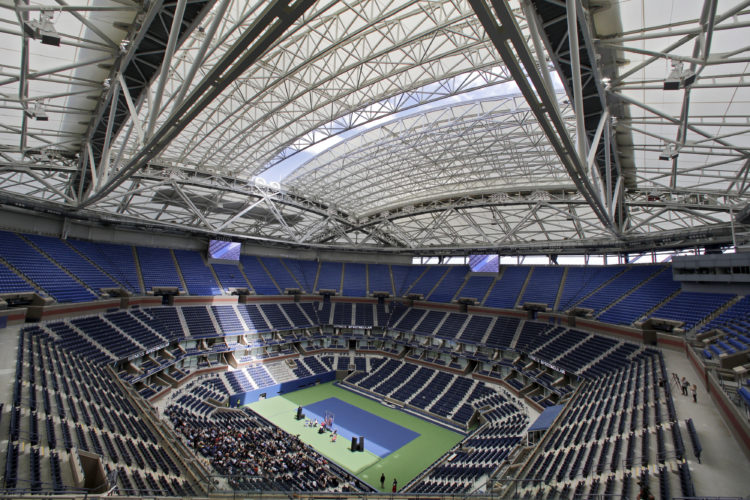 FILE - In this Aug. 2, 2016, file photo, the partially open new retractable roof allows a ribbon of light into Arthur Ashe Stadium at the Billie Jean King National Tennis Center in New York. With the stadium now covered by a retractable roof, players such as defending champ Novak Djokovic wonder how it will affect conditions when it is closed. (AP Photo/Richard Drew, File)