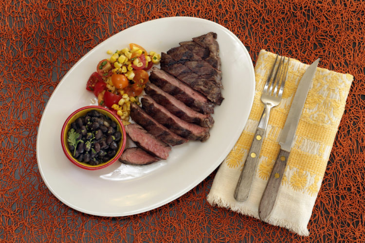 This Aug. 4, 2016 photo shows skirt steak with beer-braised black beans and corn salsa, styled by Sarah Abrams, displayed at the Institute of Culinary Education in New York. This dish is from a recipe by Elizabeth Karmel. (AP Photo/Richard Drew)
