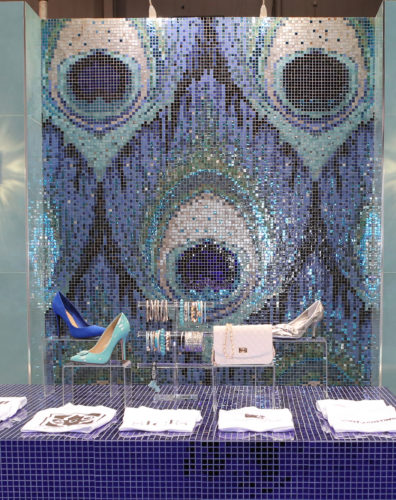 This April 2016 photo provided by Alena Capra Designs, shows an installation designed by Capra at McCormick Place in Chicago during the 2016 Coverings trade fair, where international ceramic tile and stone flooring manufacturers displayed their wares. The installation, which showcased the creative use of mosaic tiles, features a stunning iridescent peacock feather, background. (Alena Capra Designs via AP)