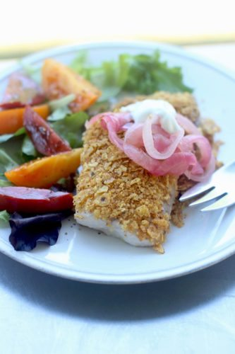 This Aug. 3, 2015 photo shows tortilla crusted tilapia with pickled red onions and crema in Concord, NH. This dish is from a recipe by Sara Moulton. (AP Photo/Matthew Mead)