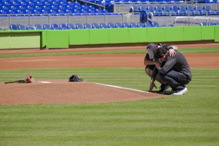 Miami Marlins player Christian Yelich, right, and teammate Justin Bour react in front of a memorial on the pitcher's mound at Marlins Park for Marlins pitcher Jose Fernanedez, Sunday, Sept. 25, 2016 in Miami. Fernandez, the ace right-hander for the Miami Marlins who escaped Cuba to become one of baseball's brightest stars, was killed in a boating accident early Sunday morning. The game between the Marlins and the Atlanta Braves was cancelled.  (AP Photo/Gaston De Cardenas)