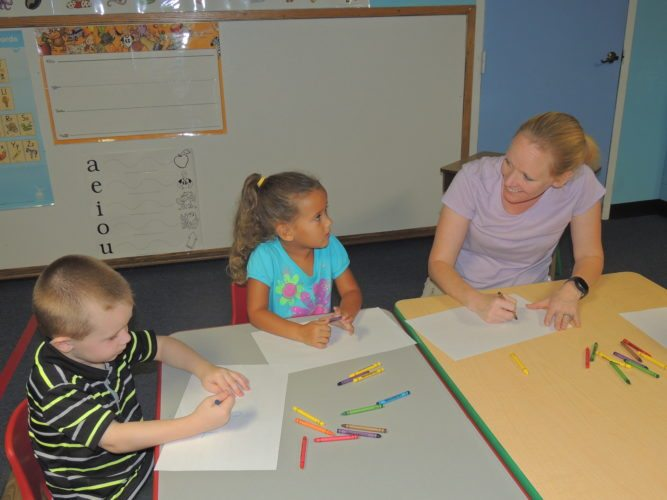 Photo by Drew Parker Marshall County Day Care Center teacher Sabrina Wise helps preschool students Bentley Dolan and Adrianna Duley with a coloring project.