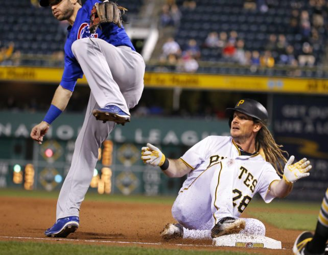 Pittsburgh Pirates' John Jaso, right, slides safely into third with a triple as the throw gets past Chicago Cubs third baseman Tommy La Stella in the seventh inning of a baseball game in Pittsburgh, Wednesday, Sept. 28, 2016. A run scored on the hit. (AP Photo/Gene J. Puskar)