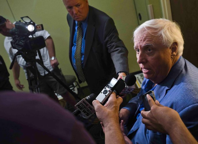 FILE - In this Tuesday Aug. 30, 2016, file photo, West Virginia Democratic gubernatorial candidate Jim Justice, right, speaks with members of the media after a roundtable discussion with representatives from various social work and mental health agencies, in Charleston, W.Va. On Friday, Sept. 30, 2016, federal officials announced that they've reached a settlement requiring $5 million in upgrades to prevent further pollution by Appalachian coal mines owned by Justice. The Environmental Protection Agency and Department of Justice announced the settlement with Southern Coal Corporation and 26 affiliates on Friday. (Christian Tyler Randolph/Charleston Gazette-Mail via AP, File)