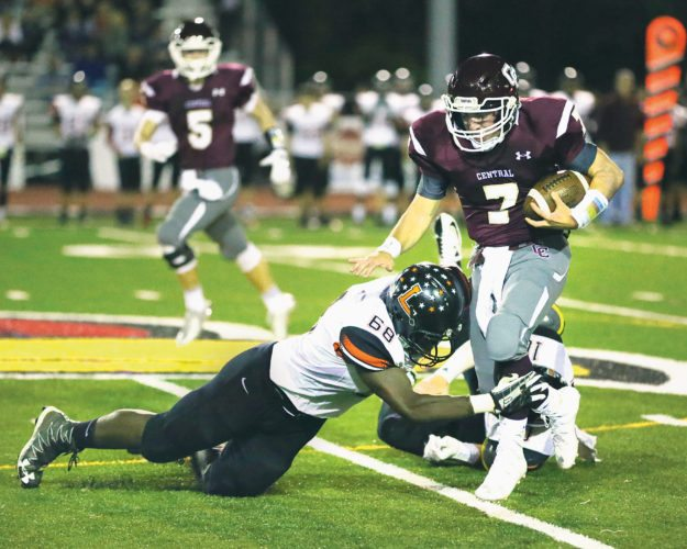 Photo by Alex Kozlowski / Wheeling Central quarterback Isaac Rine (7) tries to avoid the tackle of Linsly's Zach Oladimeji (68) during their game Friday night at Bishop Schmitt Field.