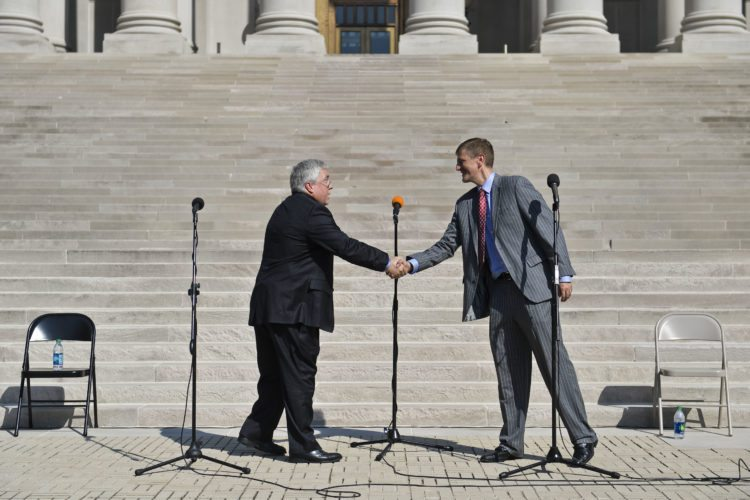 West Virginia Attorney Gen. Patrick Morrissey, left, and Democratic challenger Doug Reynolds, right, shake ands after a debate on the steps of the state Capitol building in Charleston, W.Va. on Wednesday Oct. 19, 2016. Morrisey called Reynolds deceitful, a liar and a liberal who donated to Hillary Clinton's campaign in 2007. Reynolds fired back that Morrisey is swayed by the pharmaceutical industry that has employed his wife as a lobbyist.  (Christian Tyler Randolph/Charleston Gazette-Mail via AP)