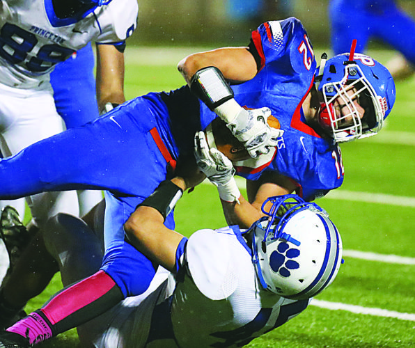 Photo by Alex Kozlowski Wheeling Park's Zach Torbett fights for extra yardage as a Princeton defender tries to make the tackle Friday at Wheeling Island Stadium.