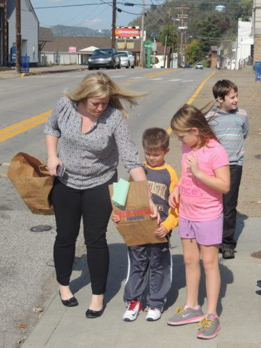 Photo by Drew Parker Center McMechen Elementary School Principal Arica Holt, left, helps organized canned food drive bags with students Noah Grigsby and Anna Cubick.